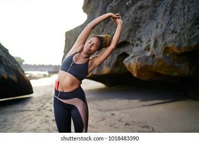 African American young fit woman dressed in active wear for training stretching body on side to strengthen muscles before morning workout while listening music in earphones connected to smartphone