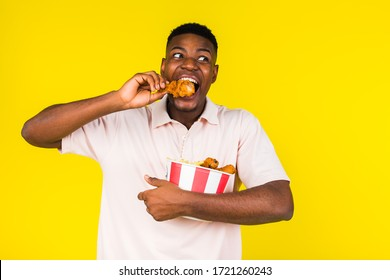 African American young guy eats fast food, chicken leg and a whole bucket in his hands. Emotions of joy and happiness, surprise. Yellow background