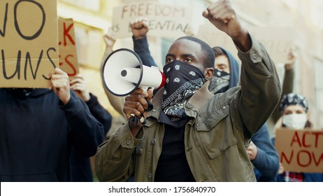 African American young handsome man in scarf on face like mask screaming in megaphone at protest for human rights outdoors. Group of people protesting at street. Strike against violence.