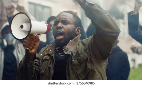 African American young handsome man screaming in megaphone at protest for human rights outdoors in smoke. Group of people protesting at street. Strike against violence.