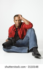African American young male adult sitting on floor with camera.
