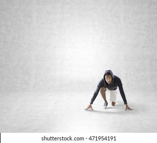 African American young man is getting ready to sprint in concrete wall room. Concept of short distance planning. Mock up