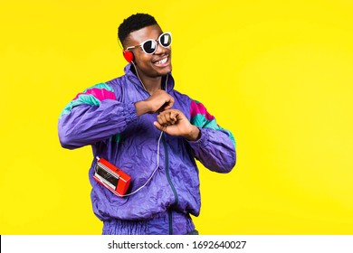 African American young man, in a jacket in the style of the 90s, with a retro cassette player, hears music, the mood of dancing and fun, yellow and purple colors
