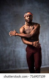 African American young man of strong physique posing in the studio for a rap music video