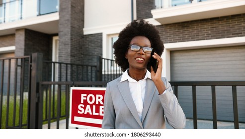 African American young stylish female real-estate agent in glasses at outskirt neighborhood and talking on mobile phone. Businesswoman looking for house and speaking on cellphone. Dwelling for sale.