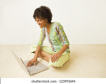 African American young woman in bright green print top sitting cross-leg on floor with laptop computer