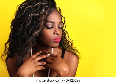 African American young woman with curly hair - easy to extend background for copy space over yellow. glamor portrait of beautiful sexy black  woman model with bright makeup with perfect clean skin.