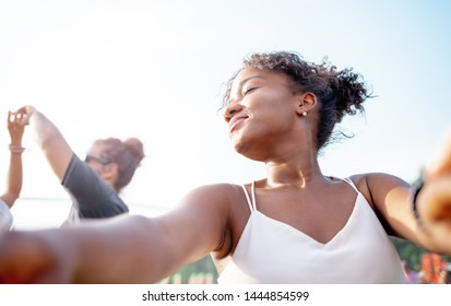 African American young woman dancing with friends at summer music festival
