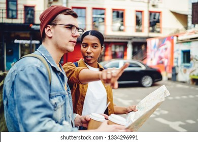 African American young woman inhabitant of city pointing hand on right direction to help caucasian tourist with map to find destination. Male traveler walking on street and search showplace in town