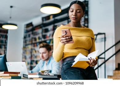 African american young woman reading incoming notification on smartphone while holding book in hands sitting in library.Dark skinned student checking mail on cellular using wireless public internet