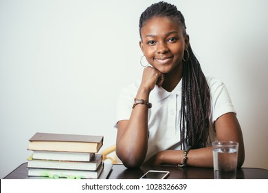 african american young woman sitting at table with books at home