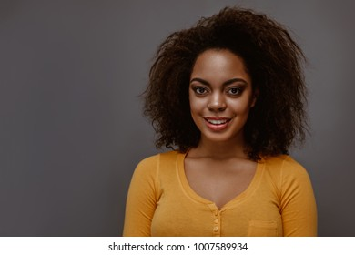 African American young woman smiling. Studio fashion portrait on gray background.