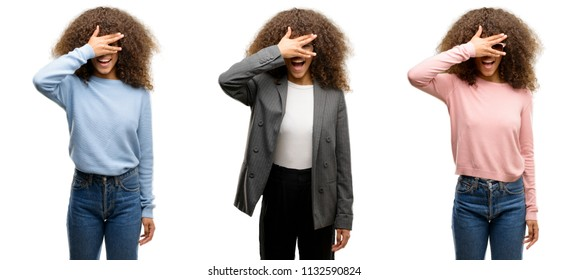 African american young woman wearing different outfits peeking in shock covering face and eyes with hand, looking through fingers with embarrassed expression.