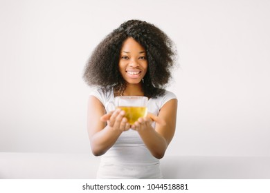 An African American young women sitting in the lotus position on white bed with cup of tea.