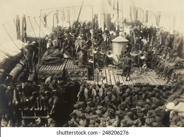African Americans with white soldiers and sailors on WW1 troop ship. July 18, 1919. Black soldiers with musical instruments have an integrated audience.
