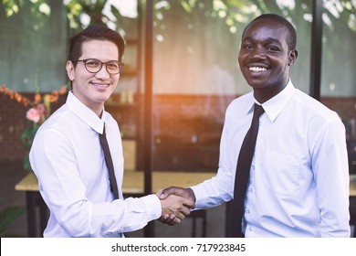 African and asian business man shaking hand with happy and smile.
