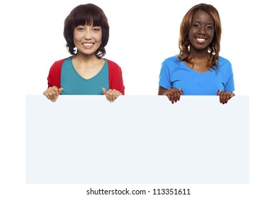 African and Asian marketing personnel holding billboard isolated against white background