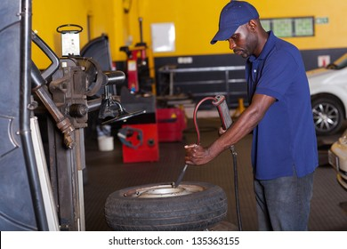 african auto mechanic pumping car tyre