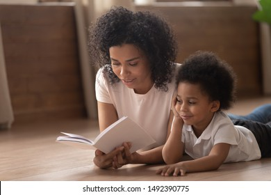 African babysitter reading book to toddler boy lying together on warm floor at home, little mixed-race son fascinated by fairy tale listens mother, improve concentration, development of child concept