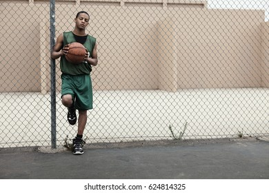 African basketball player holding ball against fence