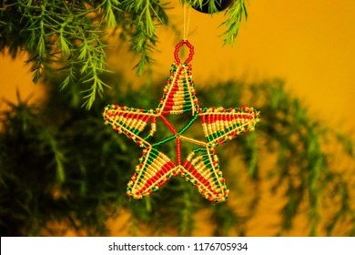 An African beaded star hangs in a Christmas tree