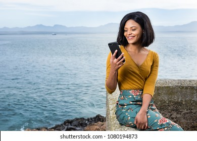 African beauty looking at her cell phone with a beautiful smile and a stunning background.