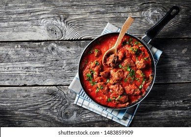 African Beef Stew in tomato sauce with spices and herbs in a skillet on an old wooden table, view from above, flatlay, empty space
