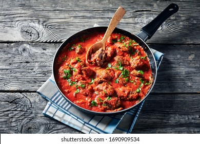 African Beef Stew in tomato sauce with spices and herbs in a skillet on an old wooden table, horizontal view from above