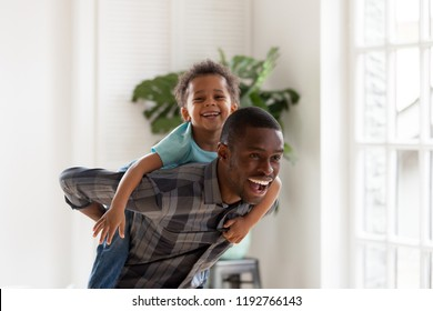 African black family spend time together have a fun standing in living room at home. Laughing father holding on back piggyback smiling cute little preschool toddler son Happy weekend free time concept