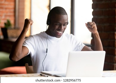 African black guy student studying at home using notebook and headphones. Happy american man clenched fists raising hands celebrating acceptance to university or getting great opportunity he was hired