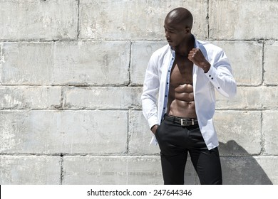 African black man model with six pack in unbuttoned white shirt, isolated against a concrete wall background on the beach
