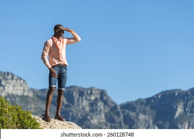 African black man, standing on a high rock overlooking Cape Town as he points and scouts the blue sky, ocean and mountains on a sunny summers day