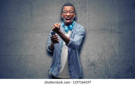 African black man student with smartphone irritated and angry expressing negative emotion, annoyed with someone