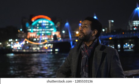 African black man walks along River Thames in London by night