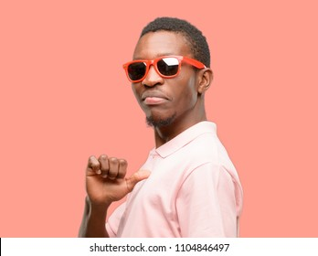 African black man wearing sunglasses proud, excited and arrogant, pointing with victory face