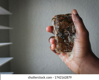African black soap with bubbles in hand