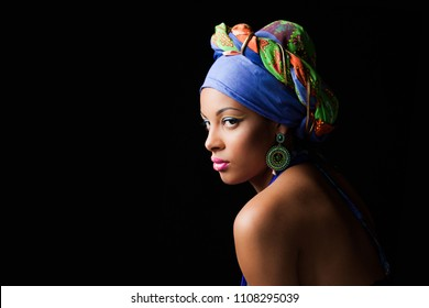 African black young woman beauty portrait with colorful turban headscarf studio shot on black