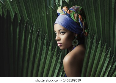 African black young woman beauty portrait with colorful turban headscarf  with palm tree leaves