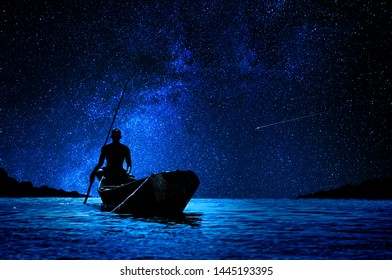 African boatman with his canoe in front of the stars