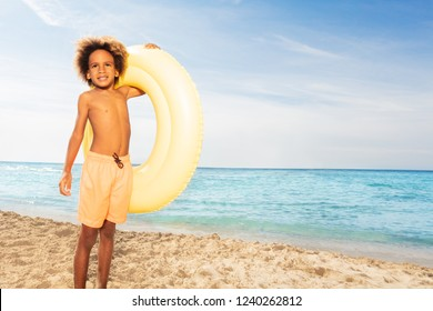 African boy with big swimming ring on sandy beach