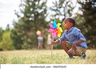 African boy blows at his pinwheel and plays