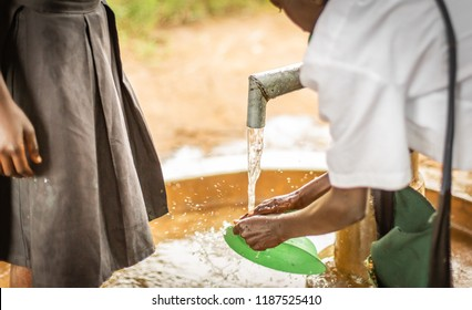 African boy cleans his plastic dish at the local town water pump.