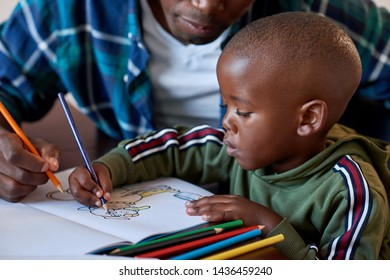 African boy drawing coloring in book, young passion interest in art