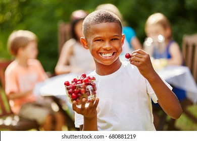 African boy eats rich in vitamins cherries laughing with joy
