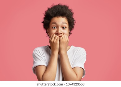 African boy feels anxious and nervous, bites finger nails, worries before perfomance at stage for first time, has puzzled expression, poses against pink background. Stressed teenager with worried look