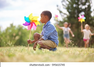 African boy and friends with pinwheels playing at the park