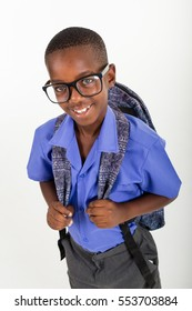 African boy with glasses wearing his school uniform and a rucksack ready to go back to school.
