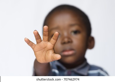 African boy holding his hand out as a STOP sign for racism and abuse