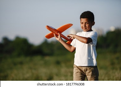 African boy holds airplane toy playing alone. Child in a summer park.