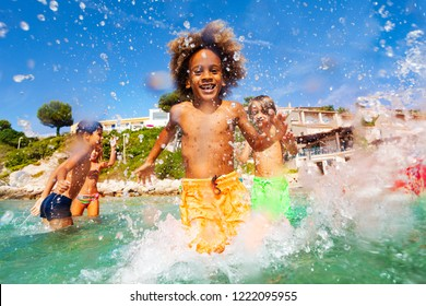 African boy playing with friends in shallow water